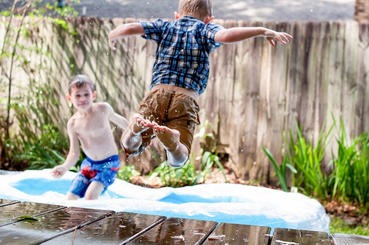 Two young boys playing on a trampoline in the backyard. One is making a huge leap onto the trampoline.