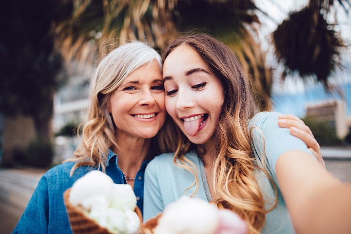 Mature mother and adult daughter having fun taking selfies with ice-cream while on summer vacations
